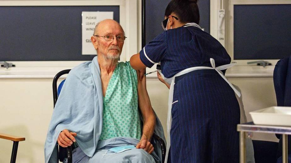 """Una enfermera administra la vacuna Pfizer-BioNtech Covid-19 al paciente William """"Bill"""" Shakespeare (izquierda), de 81 años, en el Hospital Universitario de Coventry (Foto de Jacob King / POOL / AFP) - Foto: AFP."""